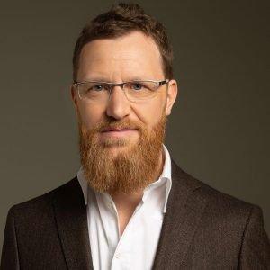 Portrait Stephan Goldmann - Ein dunkelblonder Mann mit Brille. Er trägt eine Brille, Bart sowie einen schwarzen Blazer. Darunter ein weißes Hemd.