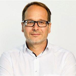Portrait Karsten Lohmeyer - Dunkelhaariger Mann mit Brille, der ein weißes Hemd trägt.
