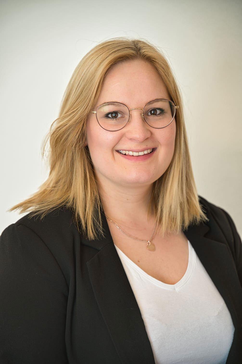 Portrait von Katharina Pompe Finanzcoach. Blonde Frau mit Brille. Sie trägt einen schwarzen Blazer sowie ein weißes Shirt.